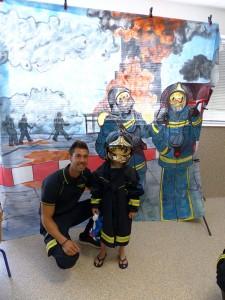 Uno de los peques con uno de los bomberos