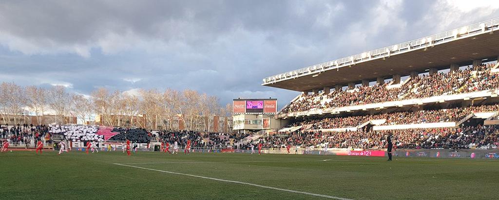 Imagen del estadio y tifo en el fondo